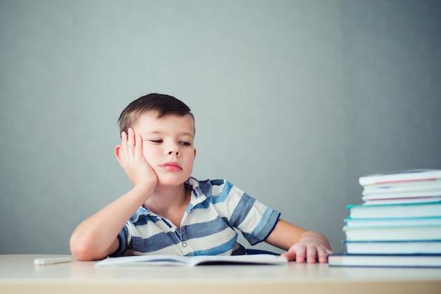 Menino infeliz fazendo lição de casa
