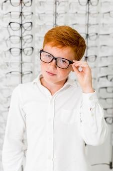 Menino inocente com pé de óculos de armação preta na loja de óptica