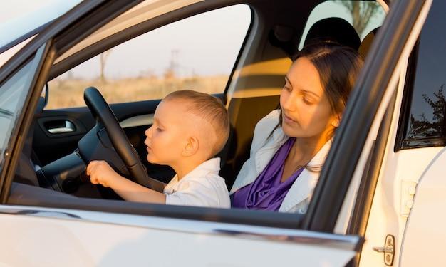 Menino inquisidor brincando com indicadores de carro enquanto está sentado no colo da mãe atrás do volante