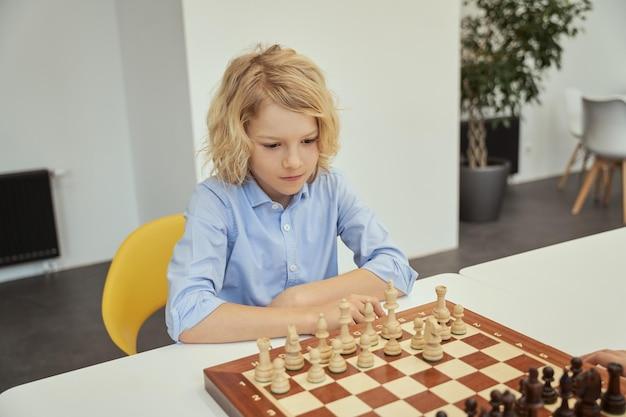 Menino inteligente caucasiano com camisa azul, jogo intelectual, sentado na sala de aula e jogando xadrez