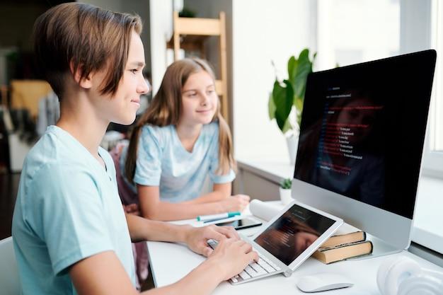 Menino inteligente e seu colega de classe olhando os dados no monitor do computador enquanto ambos estão sentados na mesa da sala de aula