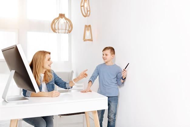 Menino inteligente. jovem feliz e encantada sorrindo e ouvindo o filho enquanto está sentado à mesa