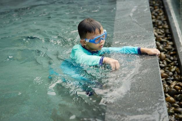 Menino joga água sozinha ao lado da piscina no conceito de verão