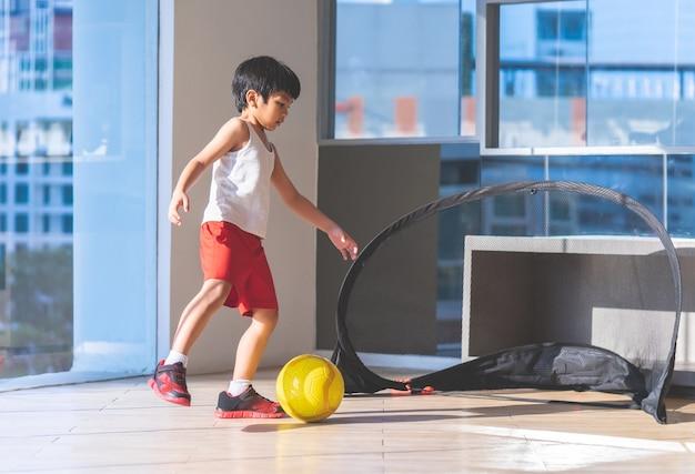 Menino jogador de futebol está pisando na bola na sala