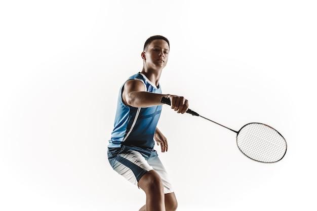 Menino jogando badminton isolado no fundo branco do estúdio. jovem modelo masculino em roupas esportivas e tênis com a raquete em ação, movimento em jogo. conceito de esporte, movimento, estilo de vida saudável.