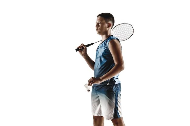 Menino jogando badminton isolado no fundo branco do estúdio. jovem modelo masculino em roupas esportivas e tênis com a raquete em ação, movimento em jogo. conceito de esporte, movimento, estilo de vida saudável. Foto Premium