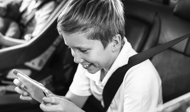Menino jogando em um smartphone no carro