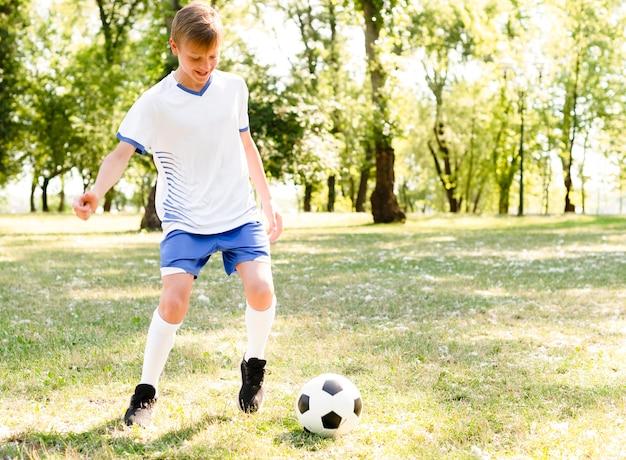 Menino jogando futebol sozinho