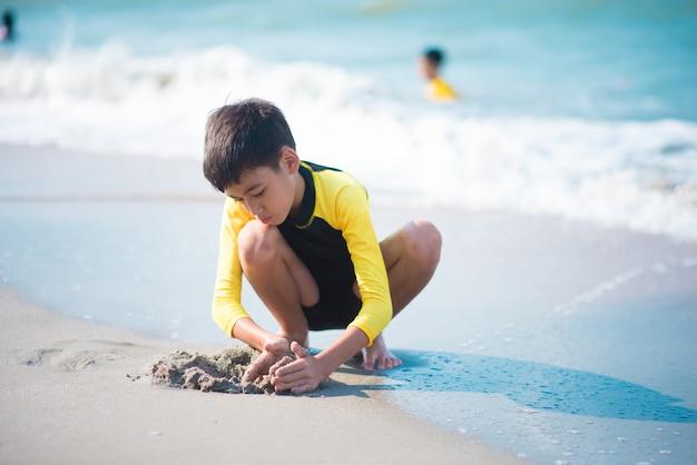 Menino jogando onda e areia na praia