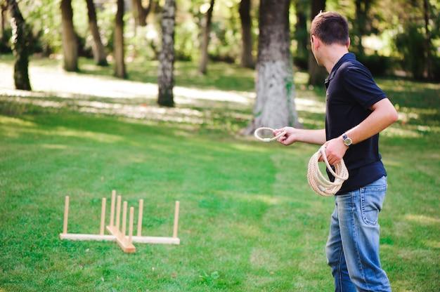 Menino jogando um jogo jogando anéis ao ar livre no parque de verão.