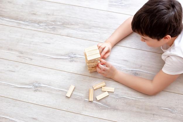 Menino jogando uma partida de jenga no chão