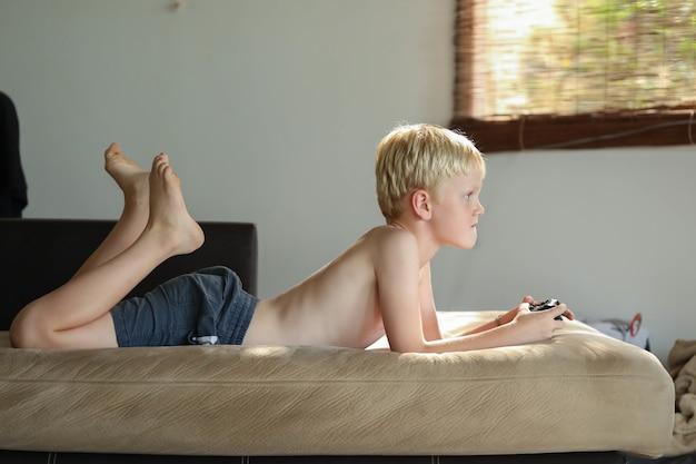 Menino jogando videogame em casa no sofá na luz suave da tarde
