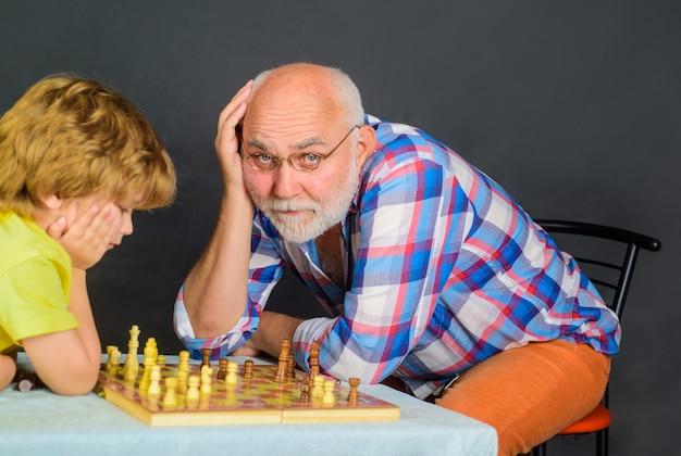 Menino jogando xadrez com a infância do vovô e jogos de tabuleiro, desenvolvimento do cérebro e conceito de lógica