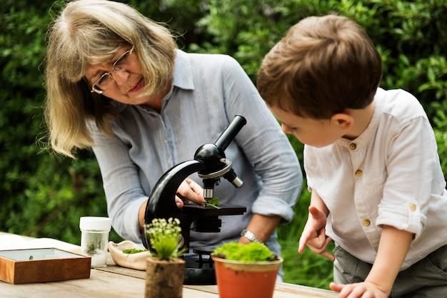 Menino jovem, aprendizagem, com, mulher velha, e, telescópio