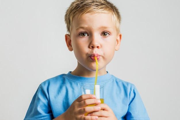 Menino jovem, bebendo suco