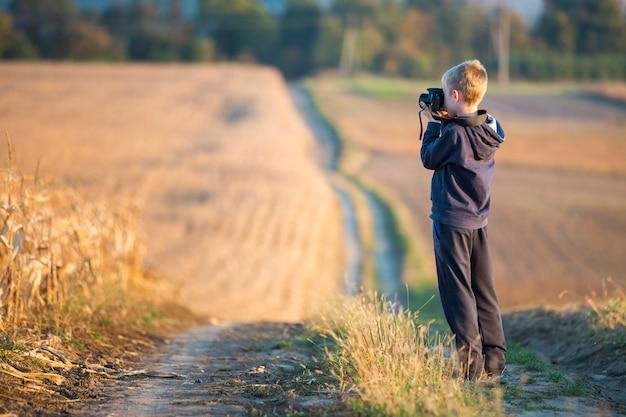 Menino jovem criança com câmera fotográfica tirando foto do campo de trigo