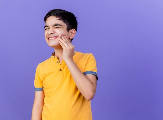 Menino jovem e dolorido, caucasiano, tocando a bochecha, tendo uma dor de dente isolada na parede roxa com espaço de cópia