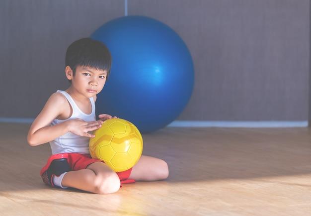 Menino jovem, é, sentando, com, futebol, chão
