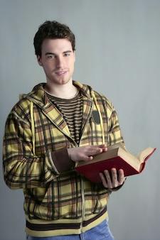 Menino jovem estudante com o livro aberto nas mãos roupas amarelas