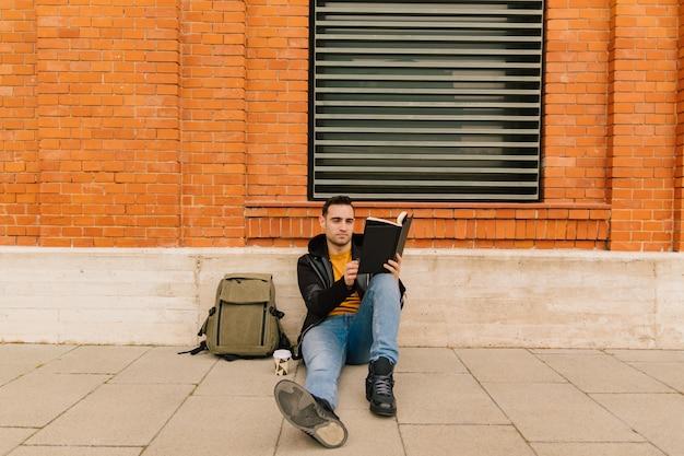 Menino jovem estudante, com traços hispânicos e latinos, lendo um livro ao ar livre na cidade. conceito de estilo de vida e cultura.