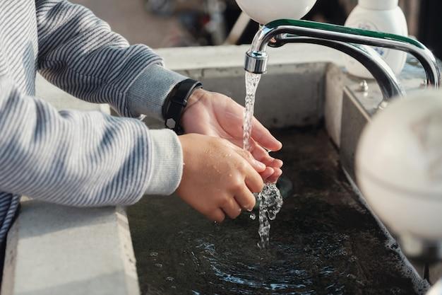 Menino jovem, lavando, seu, mãos, pia