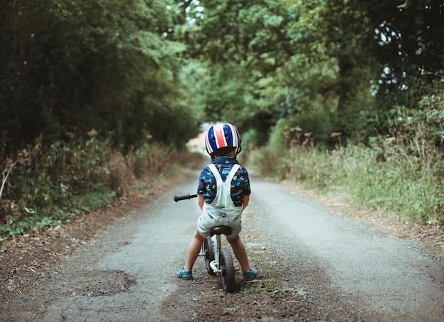 Menino jovem, montando uma bicicleta