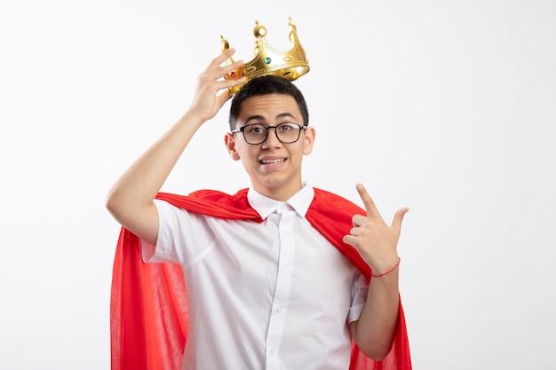 Menino jovem super-herói impressionado com capa vermelha usando óculos, olhando para a câmera, agarrando a coroa apontando para ela isolada no fundo branco com espaço de cópia