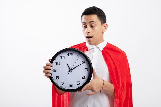 Menino jovem super-herói impressionado com uma capa vermelha segurando e olhando para o relógio isolado no fundo branco com espaço de cópia