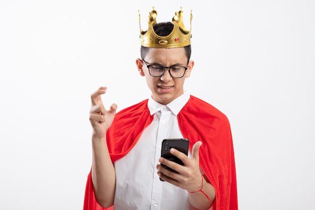 Menino jovem super-herói irritado com capa vermelha usando óculos e uma coroa segurando e olhando para o telefone celular, mantendo a mão no ar isolado no fundo branco com espaço de cópia