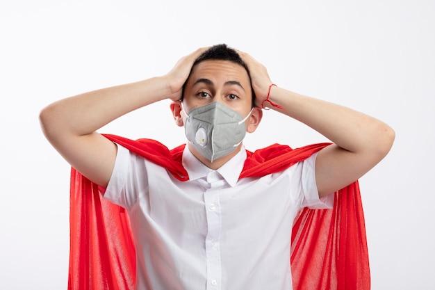 Menino jovem super-herói surpreso com capa vermelha e máscara protetora, mantendo as mãos na cabeça, olhando para a câmera, isolada no fundo branco