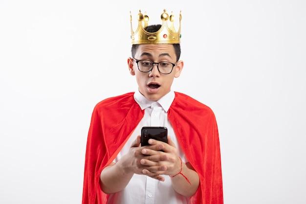 Menino jovem super-herói surpreso com uma capa vermelha usando óculos e uma coroa segurando e olhando para o celular isolado no fundo branco com espaço de cópia