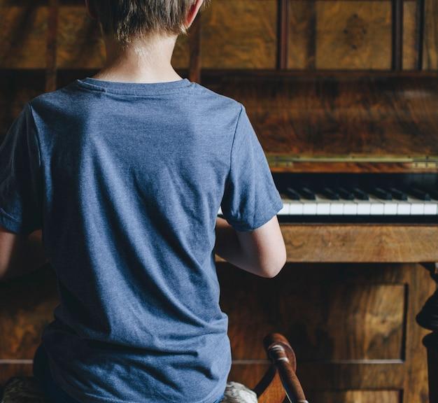 Menino jovem, tocando piano