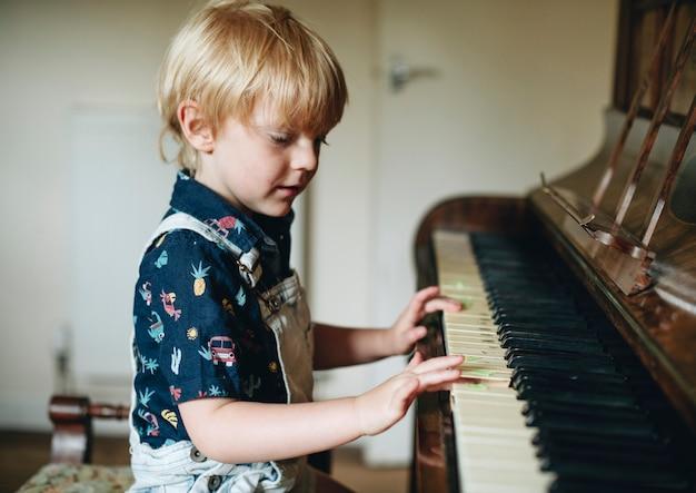 Menino jovem, tocando, um, piano