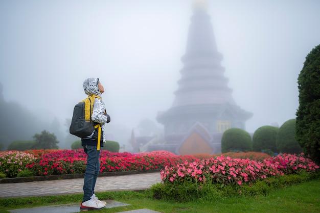 Menino jovem viajante com bolsa no belo jardim de nevoeiro.