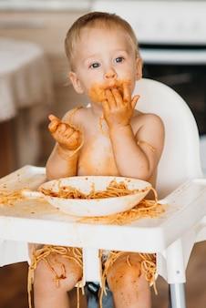 Menino lambendo os dedos após comer macarrão