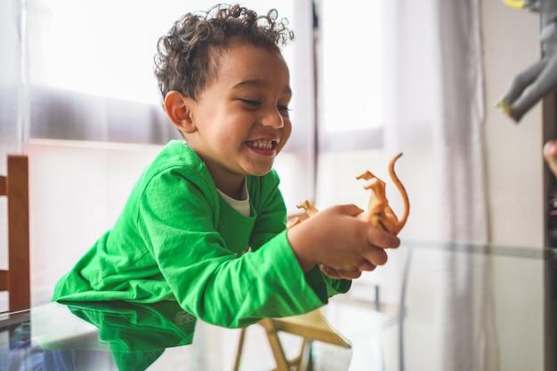 Menino latino-americano brincando com brinquedos de animais em casa