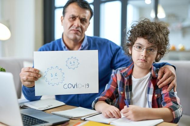 Menino latino em idade escolar sentado à mesa junto com seu pai parecendo descontente durante