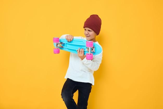 Menino legal e sorridente com um skate de chapéu vermelho e fundo isolado com as mãos