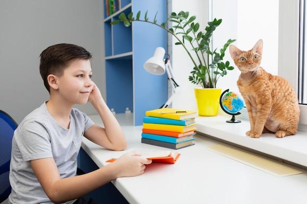 Menino lendo e olhando para o gato