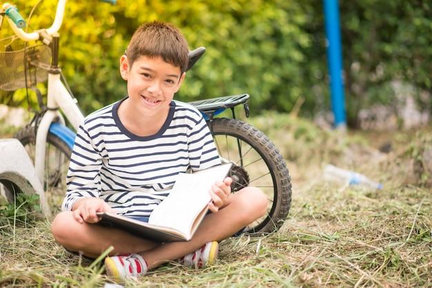 Menino lendo livro sentado com bicicleta no parque