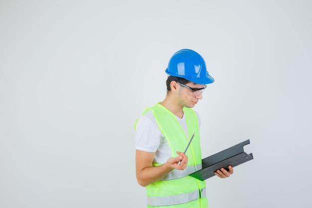 Menino lendo notas na pasta de arquivo, segurando a caneta no uniforme de construção e olhando a vista frontal focada.