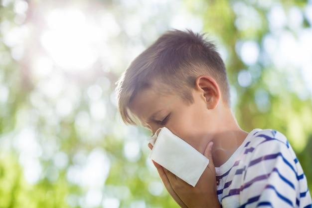 Menino limpando o nariz enquanto espirra