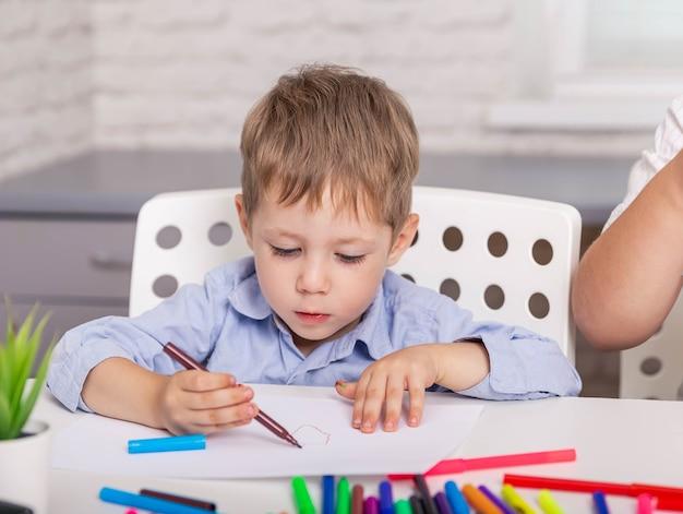 Menino lindo desenhando com lápis na aula menino concentrado