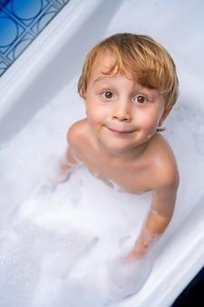 Menino lindo e loiro brincando e tomando banho na banheira