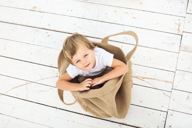 Menino lindo lindo, alegre, engraçado e feliz em uma bolsa de vime no chão de madeira branca