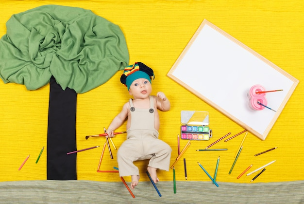 Menino lindo pintando com tintas coloridas e pincéis
