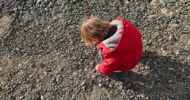 Menino lindo recolhe pedras primavera