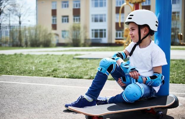 Menino lindo, relaxado, sentado no skate contra prédios amarelos