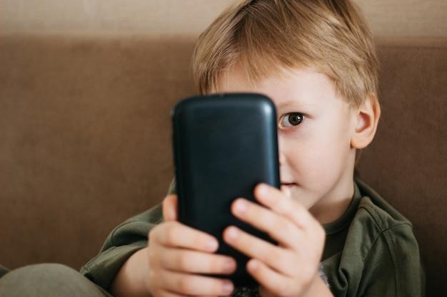 Menino lindo usa um telefone, menino caucasiano segurar smartphone.