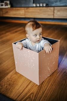 Menino loiro adorável suspeito sentado na caixa e olhando para longe. interior da casa.